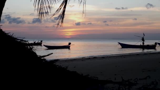 Silhouette von Fischerbooten bei orangefarbenem Sonnenuntergang