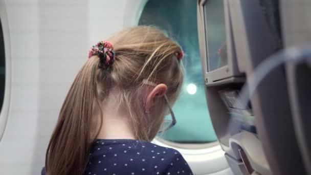 Kind schaut im Flugzeug in Fenster