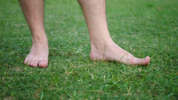 Bosé mužské kohoutky prsty na čerstvě řezanou zelenou trávu v zahradě