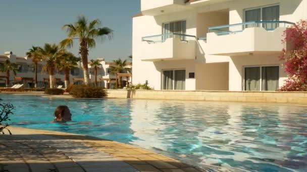 Aranyos nő úszik a medencében.