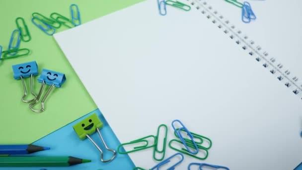 Színes gemkapocs, mosoly kötőanyag klipek és ceruzák papíron Jegyzetfüzet
