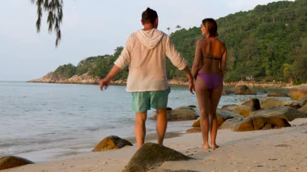 Happy couple embracing enjoying ocean during travel holidays vacation