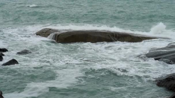 Tengervíz és hatalmas hullámok zuhannak a sziklás sziklaszirtre fröccsenő és fehér habbal