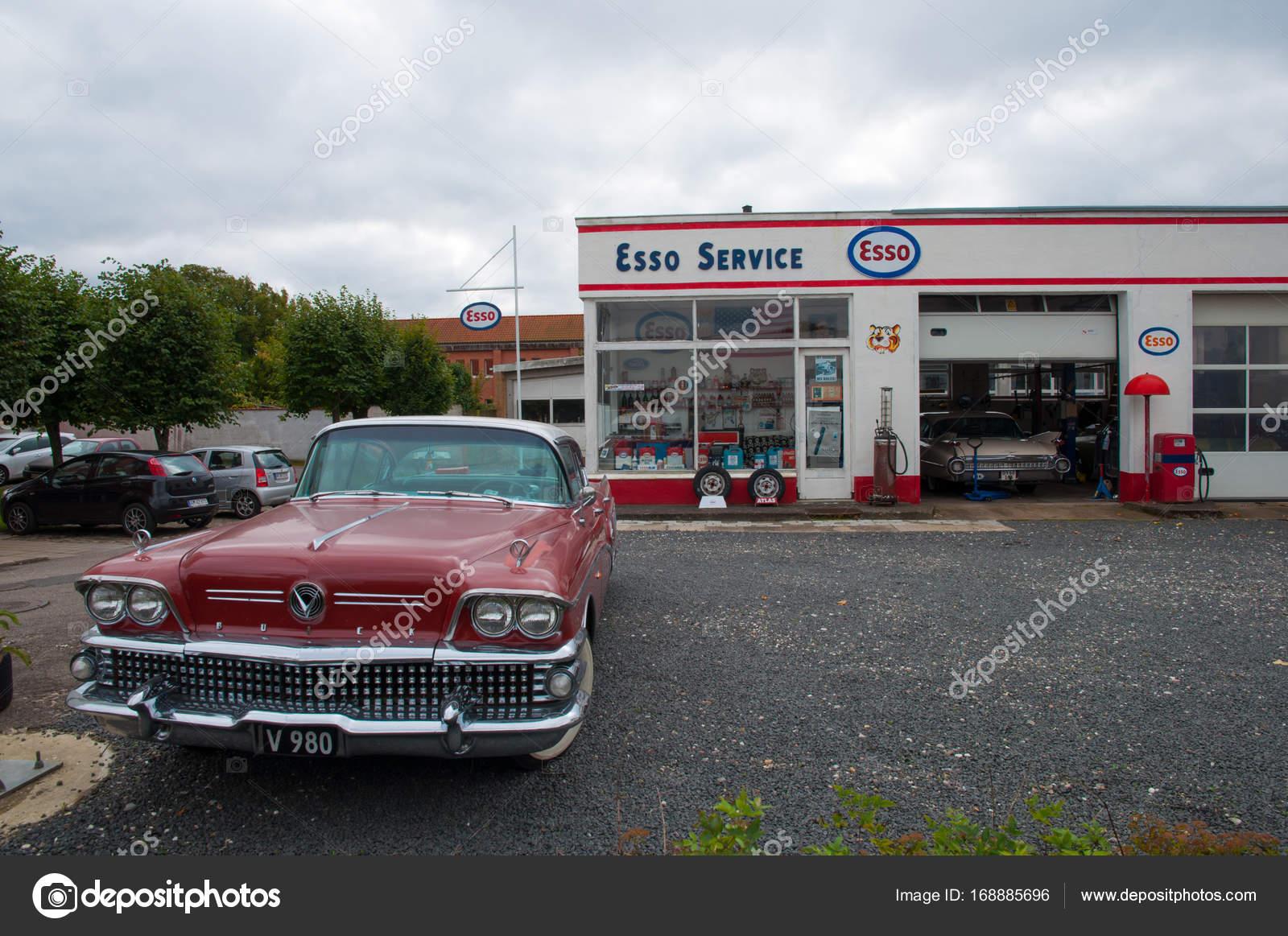 old vintage car in front of a vintage petrol station and workshop ...