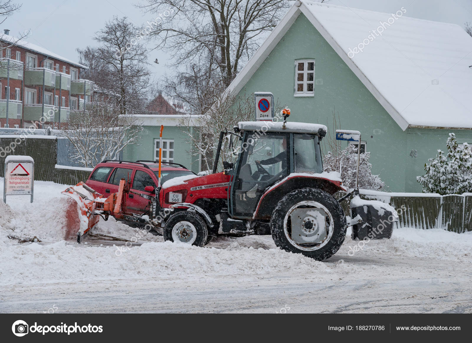 Worker on a tractor with a snow plow plowing snow – Stock
