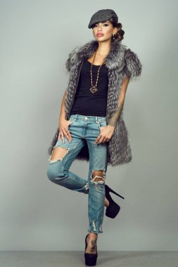 Portrait of a beautiful glam tattooed model with provocative make-up wearing silver fox jacket, ripped blue jeans, high-heeled shoes and peaked cap