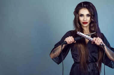 Beauty portrait of young gorgeous model with long hair wearing black silk peignoir holding curling wand and hair straightener crossed