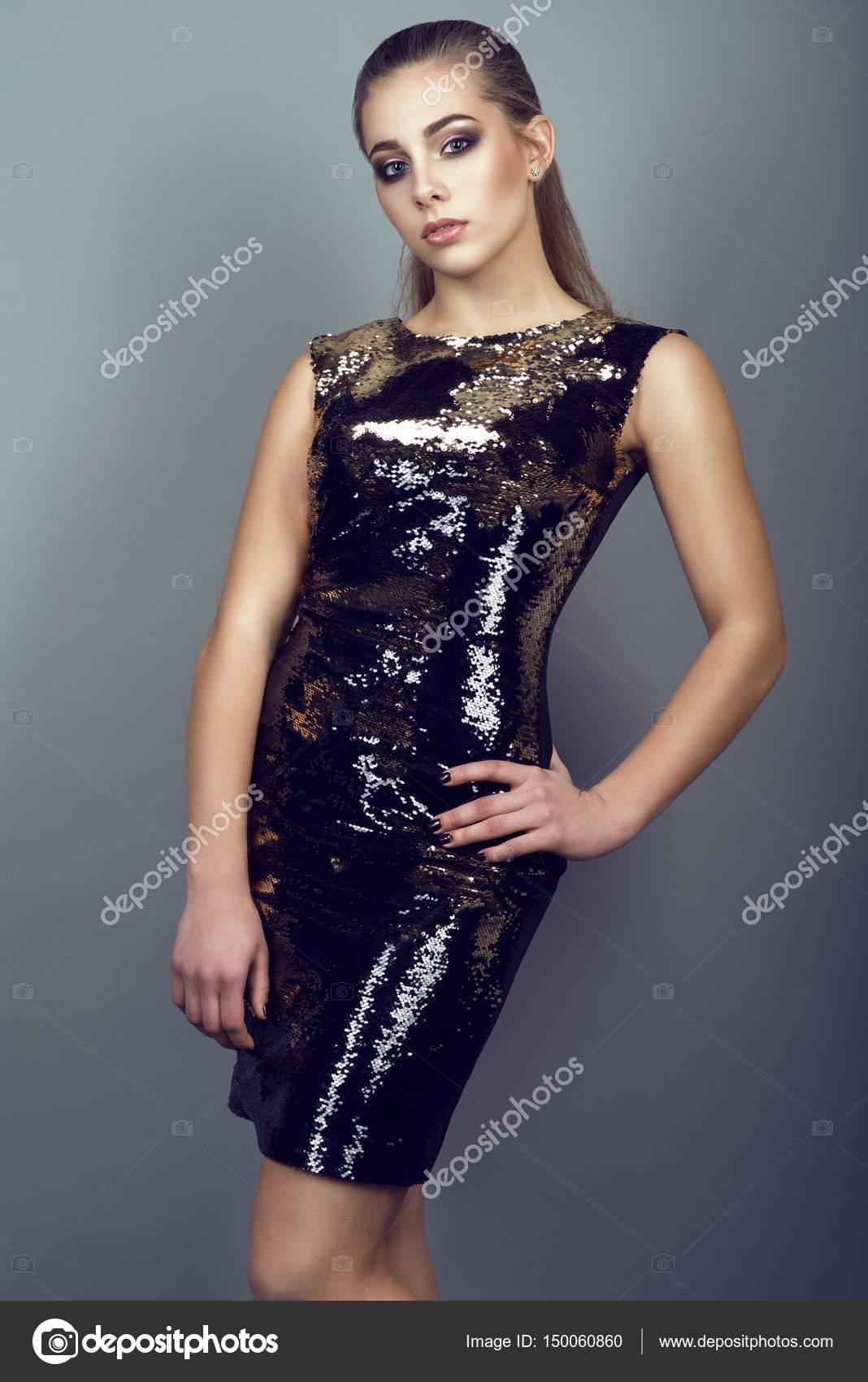 e32658e07bee3e Portret van jonge prachtige slanke model met paardenstaart en artistieke  make-up dragen strakke sequin gouden jurk staande met de hand op haar heup  op de ...