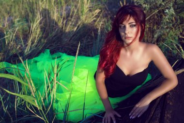 Portrait of young beautiful red haired woman in black corset and long tail green veiling skirt leaning on the shabby upside down wooden boat in the middle of the field with dry grass