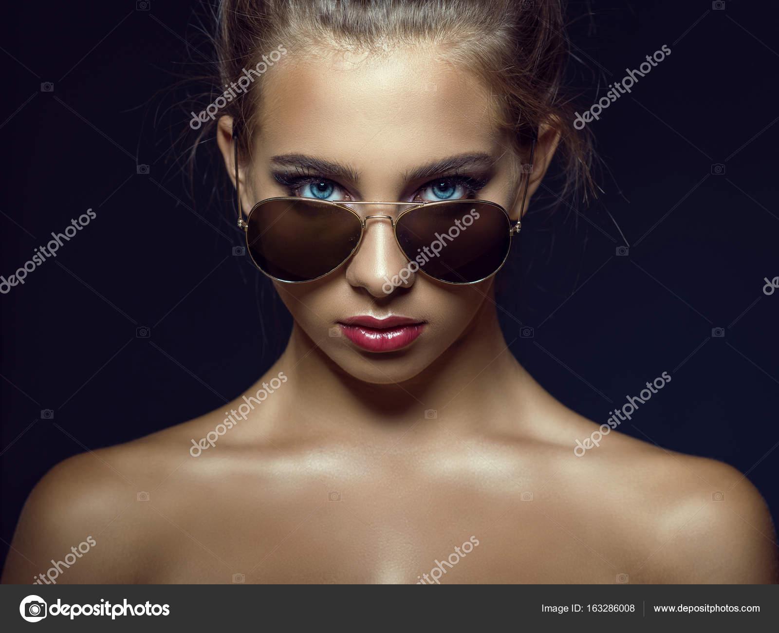 ... yeux bleus modèle avec beau maquillage et les cheveux de bébé autour de  son visage regardant droite par-dessus ses lunettes de soleil aviateur  branché. bb54ce4f2c68