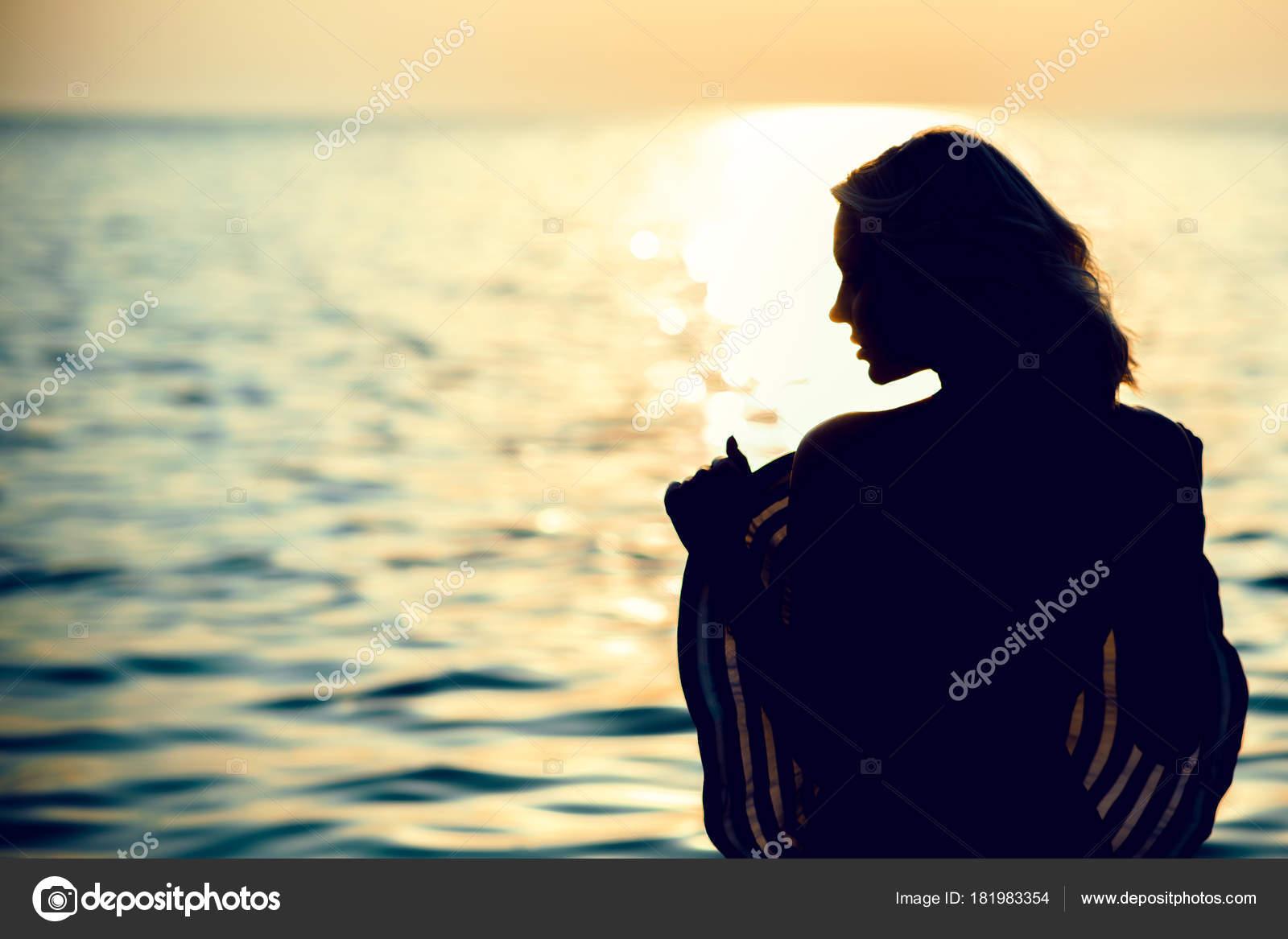 cc3d36f7c4b Σιλουέτα του μια όμορφη γυναίκα που στέκεται με την πλάτη στην ...