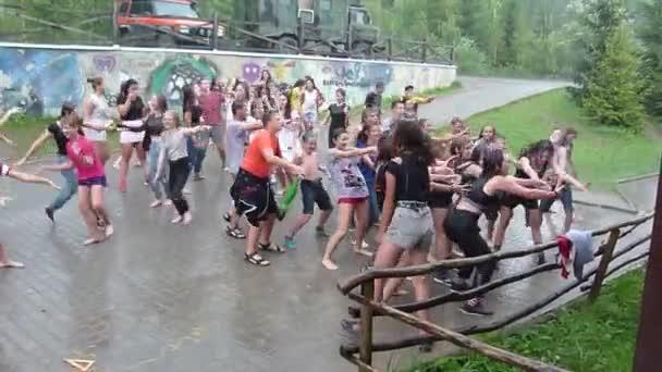 oryavchyk village, lviv region, Ukraine - 10. August 2018: Unbekannte Kinder im Alter von 8-15 Jahren tanzen im Regen im Edelweiß-Kinderlager.