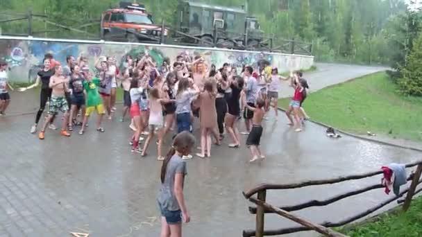 ORYAVCHYK VILLAGE, LVIV REGION, UKRAINE - AUGUST 10, 2018: Unidentified children, ages 8-15  years old, dance in the rain at the Edelweiss Childrens Camp.