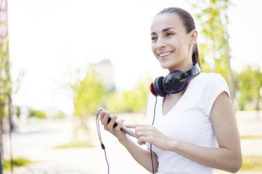 woman listening music via mobile phone