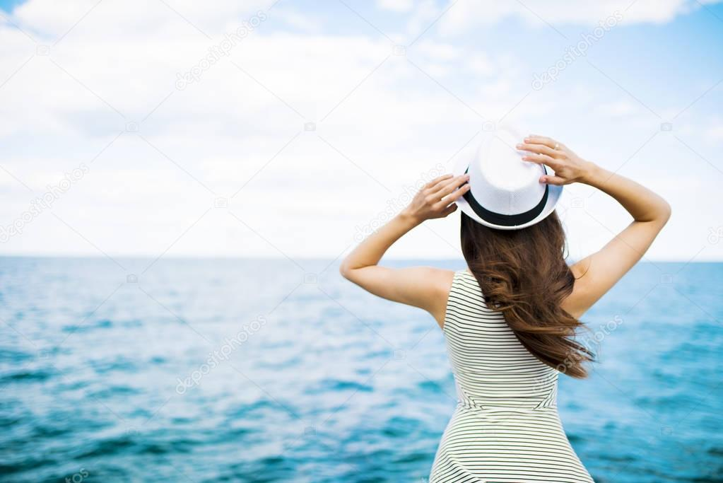 back view of woman in hat on pier