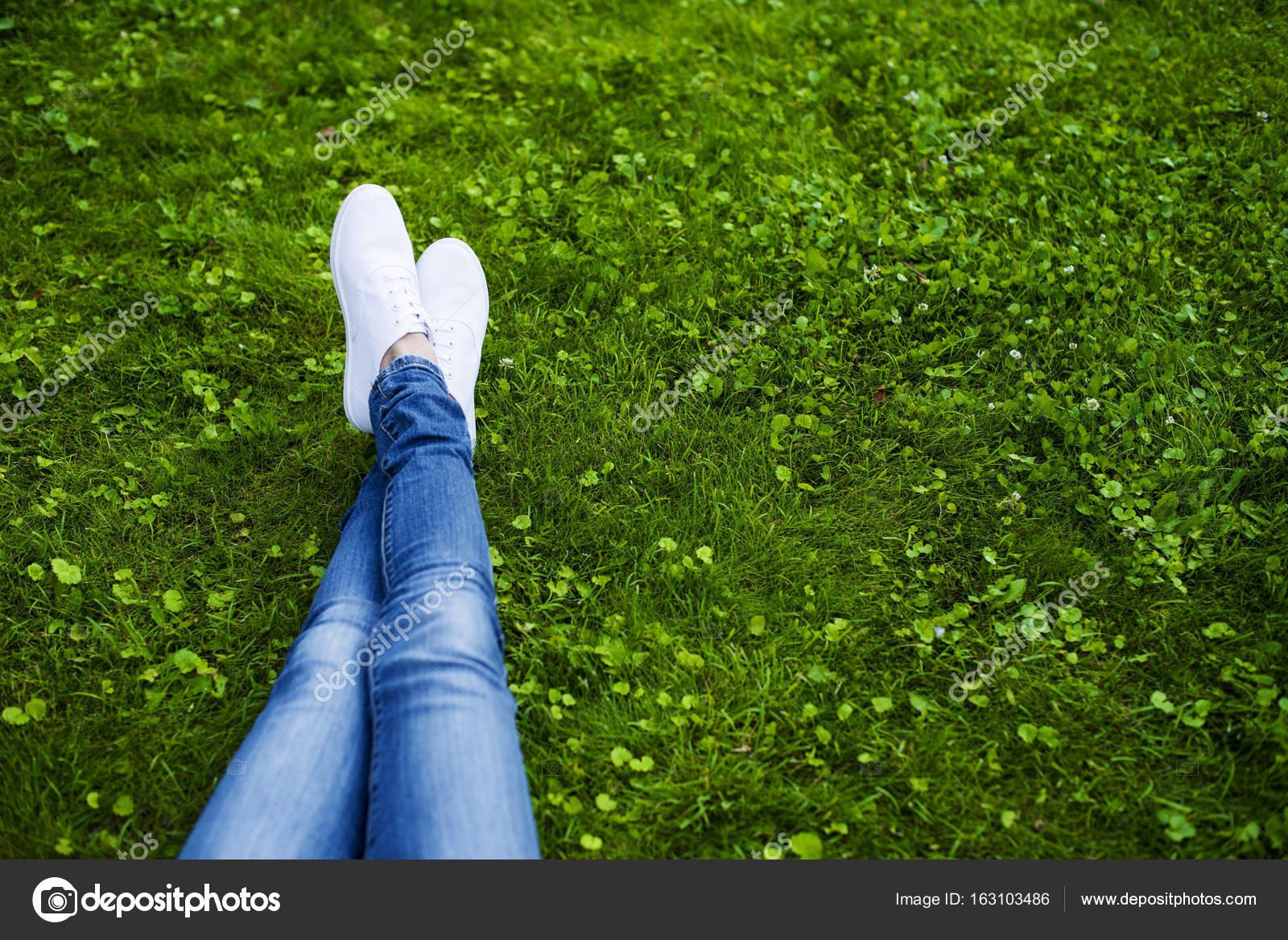 433e38fe1 Pés de mulher em tênis branco na grama verde brilhante no parque — Foto de  saragolfart@gmail.com