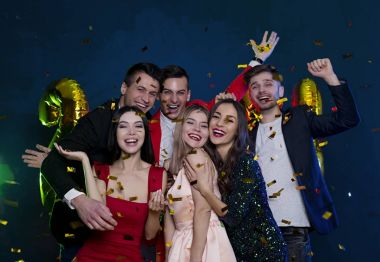 We wish you a merry Christmas and a happy new year. Happy and smiling friends at party with confetti.  People and holidays concept. Celebration and party. New year. Birthday