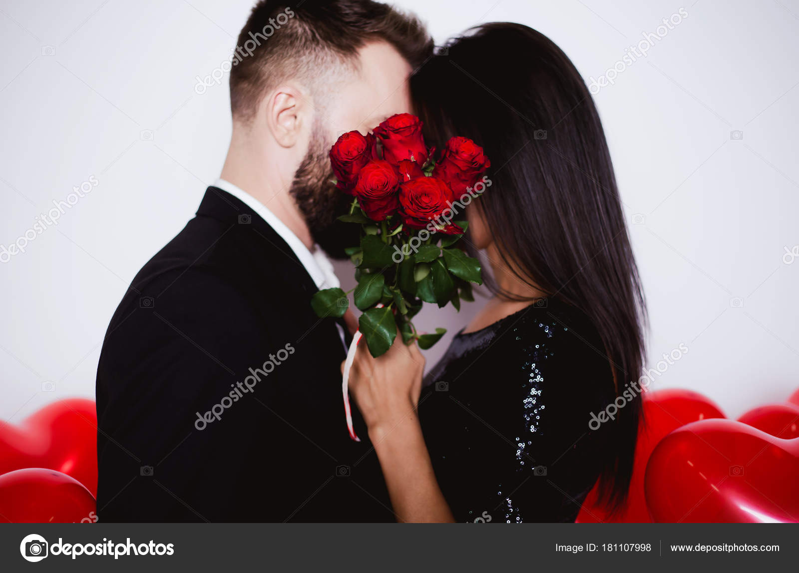 Photo Beautiful Young Couple Love Who Kisses Hides Red Roses — Stock Photo  © saragolfart@gmail.com #181107998