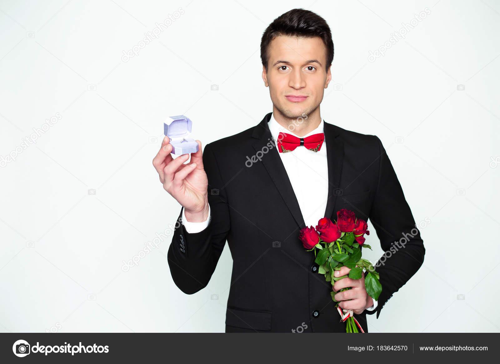 Uomo elegante moderno sicuro bello in un vestito nero ufficiale e un papillon  rosso sta tenendo una scatola con un anello di fidanzamento e belle rose  rosse ... 7a73236f8440