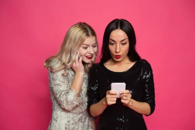 Rest with phones. Two stylish smiling beautiful women in evening dresses write messages on the phone or use the Internet on a pink background.