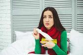 Fotografie Porträt einer jungen kranke Frau mit laufender Nase in einem roten Schal liegen auf dem Bett zu Hause und behandelt hautnah. Das Konzept von Gesundheit und Krankheit