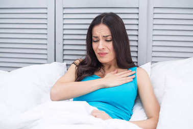 Severe pain in the heart. Young woman lying in bed at home holding a hand to her chest by a sharp pain in heart.