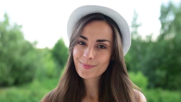 Detail portrétu atraktivní mladé moderní bruneta dívky v bílém klobouku, dívá se na kameru se smíchem strkání a šťouchání hlavou na pozadí přírody