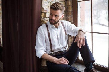 Fashion stylish confident portrair of handsome bearded guy on the big window looking away
