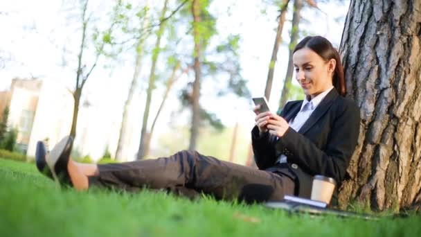 Beautiful modern business woman in a black suit is sitting in the park on a lawn under a tree and works on the phone during a break at work. Rest after hard work