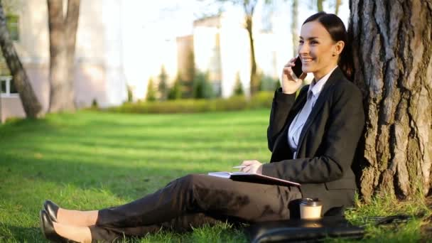 Beautiful modern business woman in a black suit is sitting in a park on a lawn under a tree and talking on the phone with her colleagues at work and writing information into a notebook