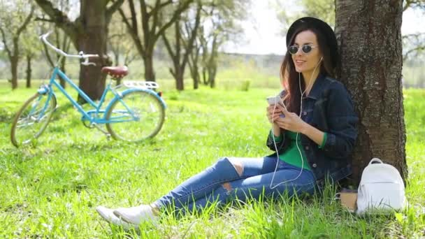 Cheerful and happy beautiful hipster woman in a hat and sunglasses listens to music with a phone in a city park and have fun on a retro bike background