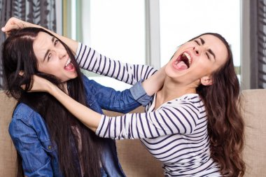 Two aggressive young women fight and wrest one another's hair.