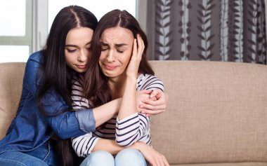 Young Girl calms down another one who are crying at home on the couch