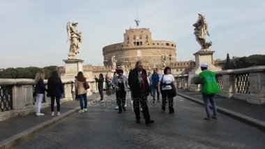 Rome, Italy - March 2017: Tourists around Saint Angel Castle and bridge over the Tiber river in Rome