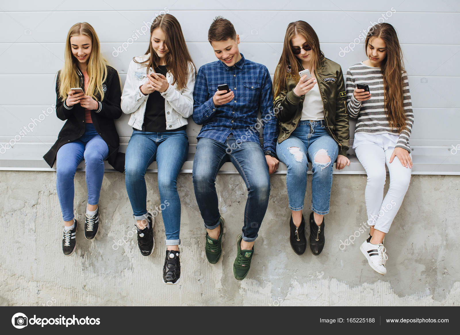 Group of teenagers outdoors with mobile phones — Stock Photo