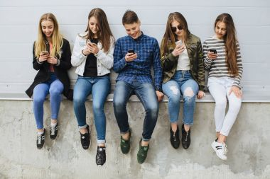 Summer holidays and teenage concept - Group of teenagers sitting outdoors using their mobile phones stock vector