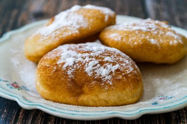 Mandazi is a slightly sweet East African Street Food; spicy, airy yeast doughnut dough made with coconut milk, flavored with cardamom and grated fresh coconut. Traditional Dish.