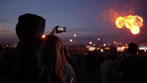 Mladý pár obdivuje noční ohňostroj ve městě