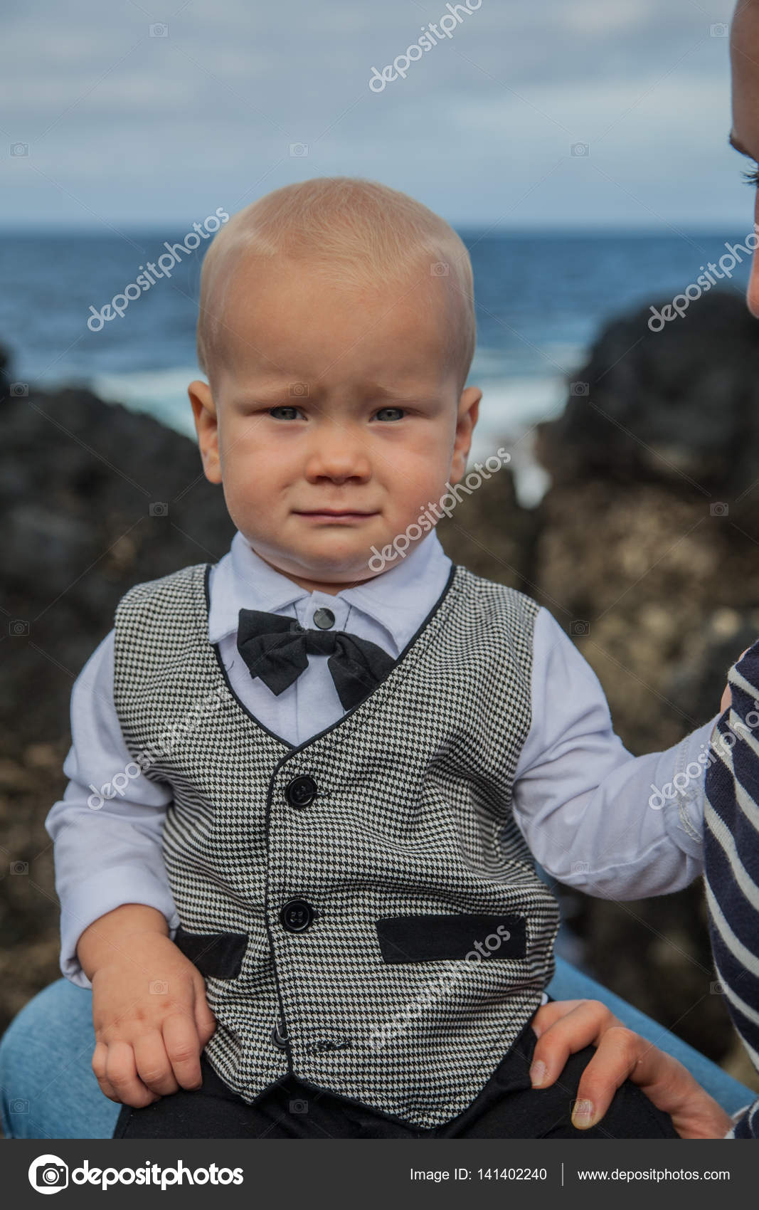 cute small baby boy smiling in formal grey suit of waistcoat outdoor