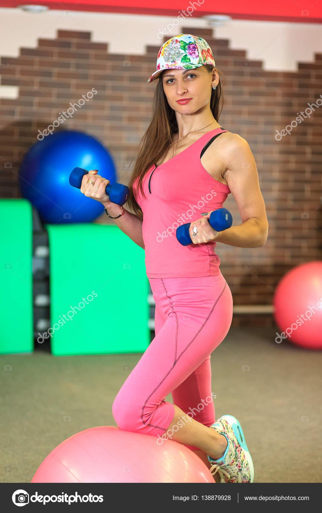 8c463574d21cd Joven hermosa chica blanca en un traje rosa deportes hace ejercicios  físicos con pesas — Foto