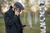 Vape gadget man. Outdoor portrait of a young brutal white guy with large beard and in a vintage cap vaping an electronic cigarette and talking on the smartphone in the birch grove in the village.