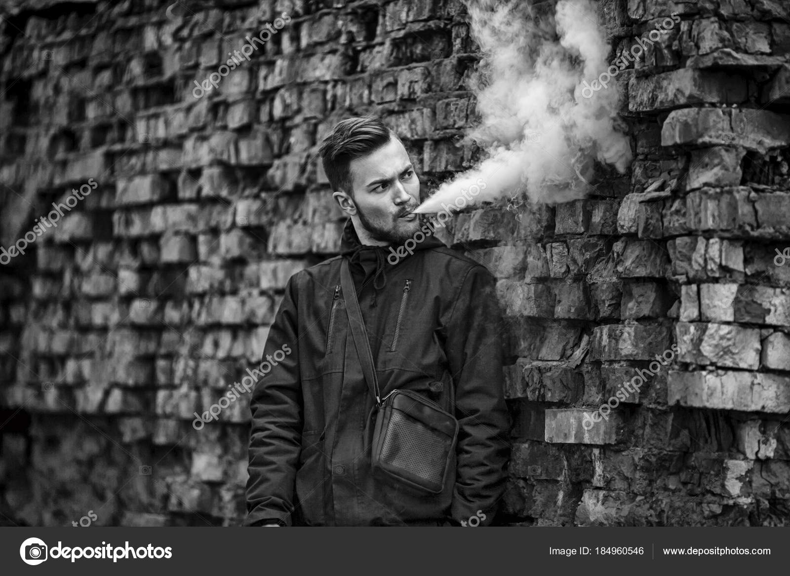 Vape man. Photo of a handsome young white guy with modern haircut in the black clothes vaping and letting off steam from an electronic cigarette near old ...