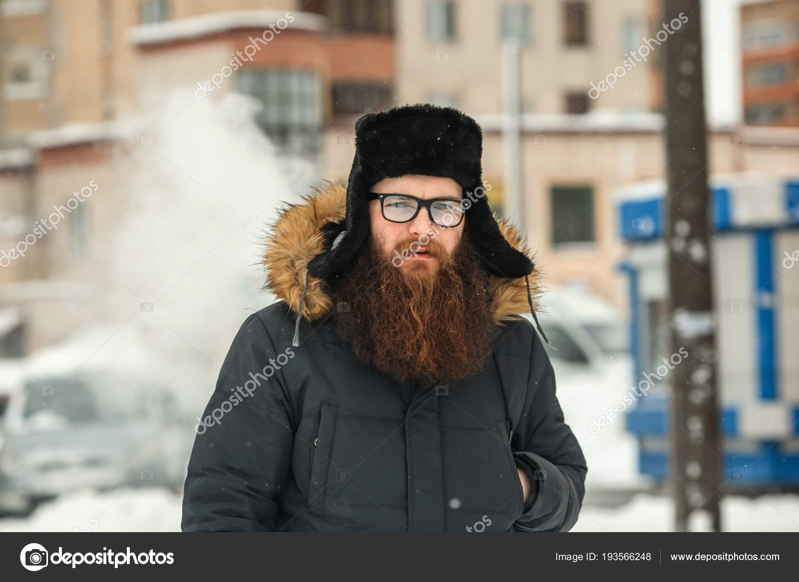 54862ddec88 Portrait of young guy with large beard in glasses and a black cap vaping an  electronic cigarette and letting out steam in the winter.