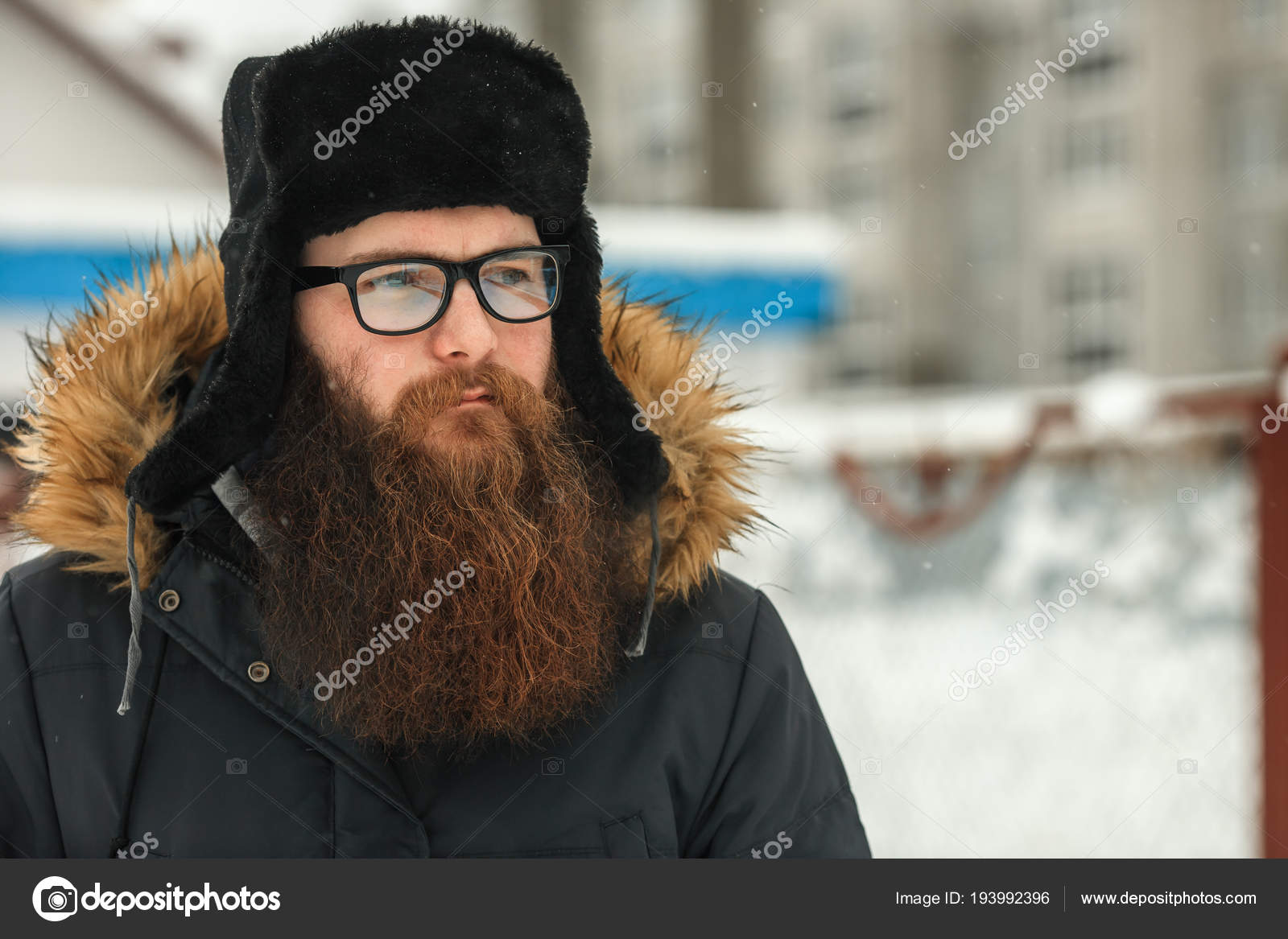 eab366bdbe5 Bearded man in real life. Portrait of young guy with large beard in glasses  and a black cap in the winter.– stock image
