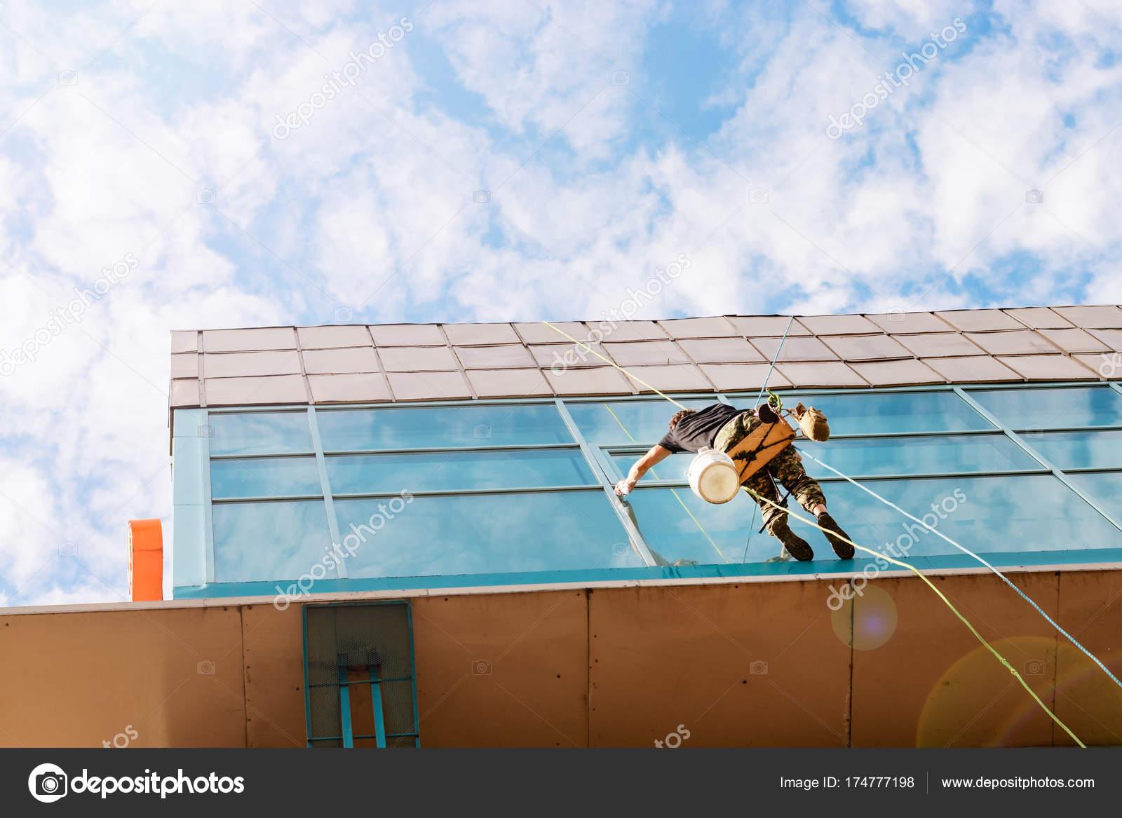 bâtiment industriel alpiniste suspendu à la corde à linge et lavages