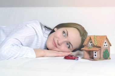 Young woman in pajamas lying on a white sofa in a room in front of a Wendy house and a car, and dreams of a bright future.