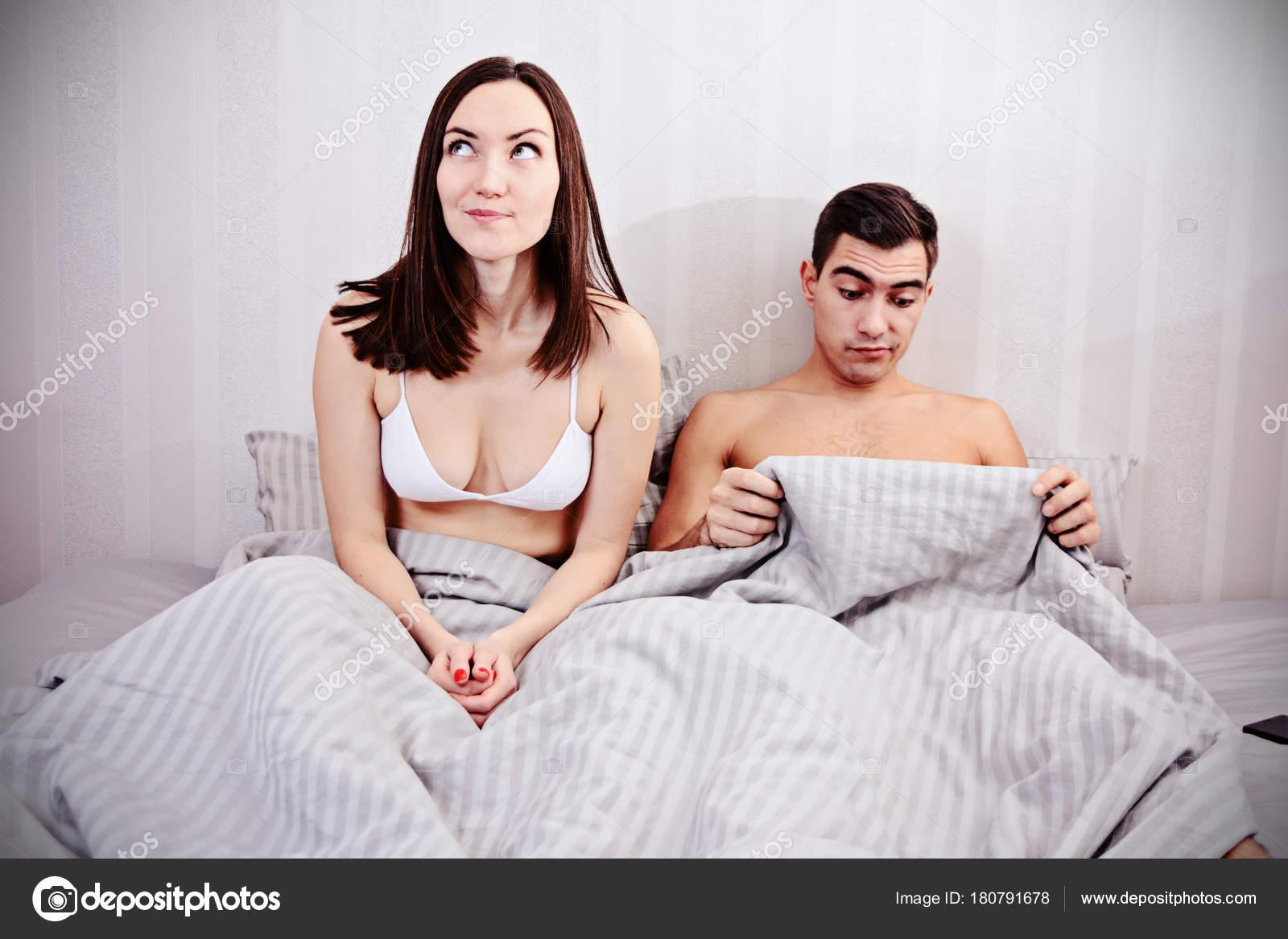 Problemi di erezione sessuale negli uomini giovane coppia nel letto la donna ride di un uomo - Problemi di coppia a letto ...