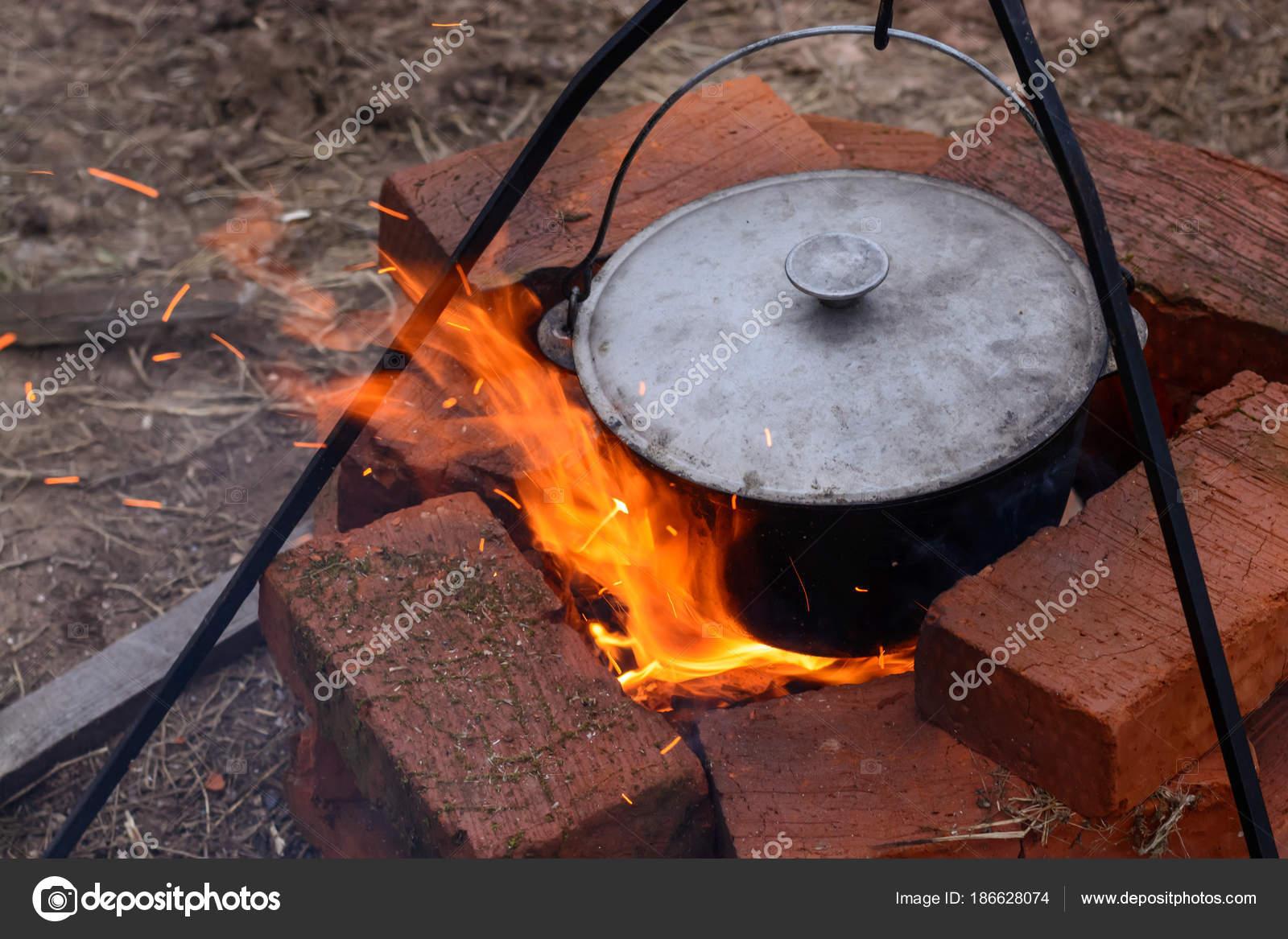 Fisch Suppe kocht in einem Kessel über dem offenen Feuer. Suppe in ...