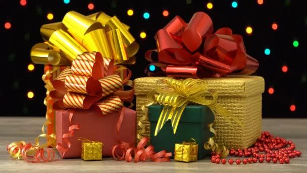 Krásné vánoční dárkové krabice a ozdoby na dřevěnou podlahu proti barevné blikající věnec na černém pozadí. Bezproblémová, opakování