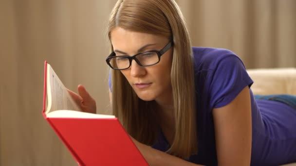 Gyönyörű vonzó fiatal nő egy lila pólót és egy fekete szemüveg feküdt a kanapén, és egy könyvet olvas. Látszó-hoz egy szótár.